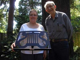 by: ELLEN SPITALERI Sherrey and Bob Meyer of Milwaukie with their Greek lyre music stand. Noteworthy Music Stands provided 35 of of the specially designed stands for the Marine Corps band to use at a recent White House state dinner.