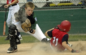 by: Dan Brood AT THE PLATE — Tigard catcher J.C. Jackson (left) looks to put a tag on Sun Creek's Smyth England.