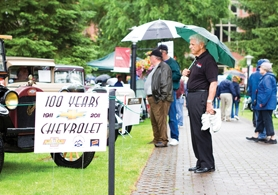 by: John Schrag Lee Wallace of Milwaukie, of the Westside Singers, paused to admire a classic Chevy after his group was rained out at Concours.