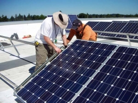 by: SUBMITTED PHOTO Eric Garcia and Ronnie Minden, electricians with Frahler Electric, installed solar panels earlier this month atop the county's Development Services Building in Oregon City.