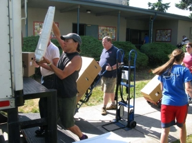 by: RAYMOND RENDLEMAN Sojourner School PTA President Alicia Hamilton (left) helps volunteers load up school items Friday afternoon to take to Linwood Elementary in Milwaukie.