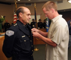 by: VERN UYETAKE  New Lake Oswego Police Chief Don Johnson was sworn-in Monday at city hall. Above, his nephew, Jeff Keith, Bend, pins his Lake Oswego badge on. Below, the new chief makes his first official speech.