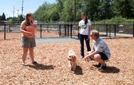 by: Alana Kansaku-Sarmiento Terri Minniti and Karen Link (from left) let Ginger off leash at the Tualatin Community dog park on Friday with Tualatin Community Services Director Paul Hennon. Ginger, the park's very first canine patron during its quiet opening, will have more company during the grand opening on Aug. 13.