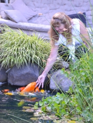 by: John Brewington IDYLLIC SETTING—Jan Campbell has made a lovely koi pond on her one-acre property in Warren. Campbell enjoys feeding the 15 koi, which are enthusiastic dinner guests. They'll even nibble on a finger if you let them.