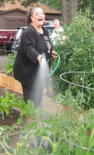 by: Barbara Sherman FUN IN THE GARDEN — With Barbara Stevens looking on in the background, Vicki Barnard finishes watering her vegetables in the King City community garden and prepares to take aim at the photographer.