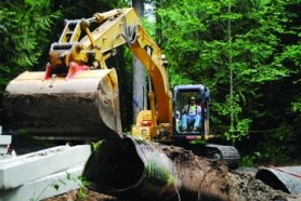 by: Tyler Graf CULVERT PULL — Tim Hill of Aquatic Contracting works an excavator's coupler so it can pull upright an old culvert from Cox Creek, near St. Helens. The Scappoose Bay Watershed project will replace the old culvert with a much larger one.