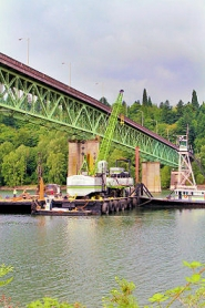 by: David F. Ashton A drilling rig prepares to take soil samples beneath the Willamette River as a first step in rebuilding the Sellwood Bridge.