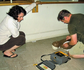 by: Elizabeth Ussher Groff Ann Steigerwald looks on, as Gavin Carpenter practices using an Automatic External Defibrillator (AED), at a recent PP&R first aid training for Woodstock Community Center volunteers.