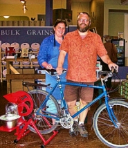 by: Rita A. Leonard Ardenwald residents Kristl and Doug Bridge show a model of the GrainMaker bicycle grinder, used for making your own flour, in their new Sellwood store.