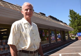 by: VERN UYETAKE Mike Buck of the Lake Grove Business Association stands by the area's new Sherwin Williams paint store.