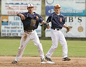 by: Miles Vance TURNING TWO — Suburban Door shortstop Nathan Suyematsu (left), with second baseman Jon Fishback behind him, makes a throw to first base to complete a second-inning double play in the game with Jesuit.