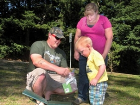by: Jim Hart Brandon Tidd of Sandy along with his wife, Hillary, and their son, Dallas, 2-1/2, inspect the contents of the Old Sawmill geocache they found in Sandy..