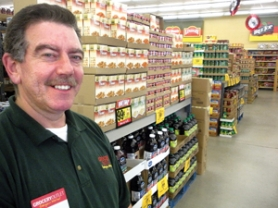 by: Jim Hart Sandy Grocery Outlet Owner and Operator Tim Thompson is pictured amid the many staples available at significant price reductions.