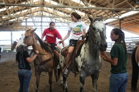 by: JAIME VALDEZ Shoni Schimmel (left) and her sister, Jude, prepare to ride horses during last week's visit to the Pendleton area by the Louisville women's basketball team.