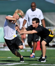 by: JOHN LARIVIERE Jonnie Penn, left, of the MTV reality series 'The Buried Life,' dodges fellow cast member David Lingwood in a charity football game at Tigard High School Saturday.