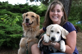by: Jaime Valdez Katie Rule-Witko, the executive director of Autism Service Dogs of America's Doggie Day Camp, cuddles Frankie, a 2-month-old golden retriever and Ike, a 4-month-old yellow lab.