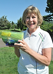 by: ERIC YAILLEN SHE'S TOPS – Former Westview boys golf coach Joan Edwards-Powell poses with her trophy after winning the Senior Division of the Oregon Women's Stroke Play Championship on Sunday.