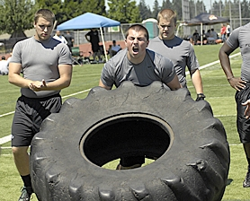 by: Dan Brood SUPER STRONG — Jarrad Schulte, a Tigard High School senior-to-be, powers the weight up during the tire flip competition at the Metro Area Lineman Challenge.