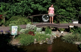 by: Jim Clark Rita Alm stands on the bridge that arches over the artificial stream built by her husband, Richard. The Alms' garden, which is completely organic, is one of eight that is featured in this year's Eastside Garden Tour from 9 a.m. to 4 p.m. Saturday, Aug. 20.