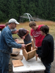by: Jim Hart Carl Lovick, left, works with youths in the Project Payback program, teaching them how to build owl boxes for the day-use recreation area near the Sandy River. Lovick is director of operations for Wilderness International, which supervises the project for BLM.