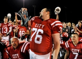 by: JOHN LARIVIERE Oregon City High School alumni captain Brent Herren receives the Battle of the Bridge trophy after the Pioneers defeated rivals West Linn 23-14.