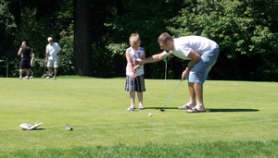 by: Jim Clark A father teaches his son how to putt at Glendoveer Golf Course.
