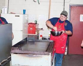 by: Chase Allgood Gaston Rural Fire District volunteer firefighter Tyler Reynolds stirs up a batch of pancakes during the annual fire department pancake feed.