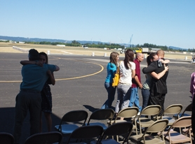 by: Chase Allgood Hope Gallinger-Long, wife of Ryley Gallinger-Long, and his twin brother Wyatt (far right) embrace last week at Hillsboro Airport before making the trip to Forest Grove with Ryley's remains. The Navy medic died Aug. 11 while on duty in Afghanistan.