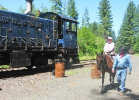 by: Barbara Sherman GOING BACK IN TIME — During the King City Travel Club's adventure on the Chelatchie Prairie Railroad on July 23, Therese Lyons hitches a ride on a horse that earlier in the day was used by train robbers.