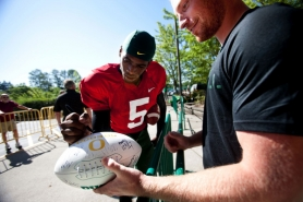by: CHRISTOPHER ONSTOTT Ducks quarterback Darron Thomas signs an autograph after a football practice last week in Eugene.