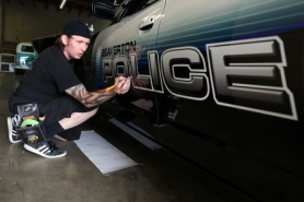 by: Jaime Valdez Kolor Werx owner Kevin Mead works on detailing the new decals of a Beaverton police patrol car Tuesday morning at his shop in Southeast Portland. This Dodge Charger displays the future look for vehicles in the agency's patrol and traffic divisions.