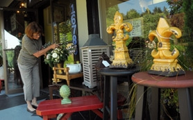 by: vern uyetake Ramona Martinson sets up her morning display at Pastiche on Bryant Road in Lake Oswego, featuring affordable home decor items. Recently, the store expanded to include both sides of the historic building.
