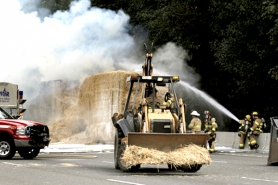 by: Jaime Valdez Firefighters sprayed water on bales of hay that caught fire Tuesday afternoon on Interstate 205. The fire damaged a tractor-trailer and blocked traffic for hours.