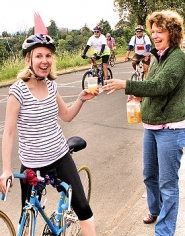 by: David F. Ashton Dr. Chloe Shanley accepts a Mimosa from Sellwood neighbor Michelle Eraut during this unauthorized stop on the Bridge Pedal ride, opposite Sellwood Park.