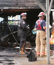 by: David F. Ashton Fire investigators begin an initial look at the fire scene, where flames injured one man.