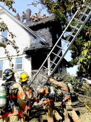 by: Courtesy of PFR Firefighters tried to stay cool in high temperatures Sunday afternoon while fighting a blaze at a three-story house on Southeast 32nd Avenue.