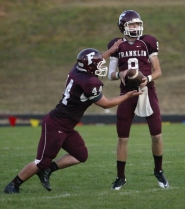 by: JIM CLARK Franklin quarterback Josh Nine (right) hands off to Cody Croydon during Friday's game with Reynolds.