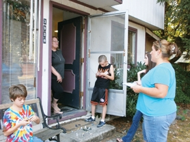 by: Christian Gaston and Nancy Townsley Canvassers Melinda Fischer and Ellie Ashby (far right) talk to Tamarack Way resident Toni Jones (in doorway) about a recall effort against two Forest Grove School Board members. Jones signed the petition.