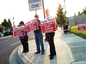by: Christian Gaston and Nancy Townsley Recall supporters Jennifer Heuer (left), Bill Bash (center) and Kevin Harmon (right), wave signs urging voters to cast their ballots in a recall election targeting the city's mayor, Neal Knight, and two city councilors, Jamie Minshall and Mari Gottwald.