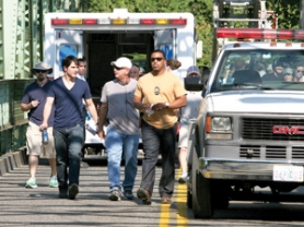 "by: Jim Clark David Giuntoli, from left, who plays Nick Burkhardt, director Michael Waxman and Russell Hornsby, who plays Lt. Hank Griffin, walk through a scene rehearsal for ""Grimm,"" on Friday at the Troutdale Bridge."