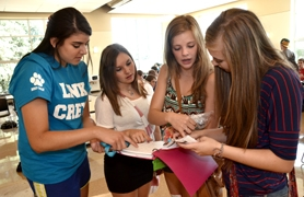 by: vern uyetake Link Crew member Izzy Romero, at far left, helps freshmen, from second to left, Courtney Landis, Brianna Dyrdahl and Sidney Kolasinski at West Linn High School during their first day of school.