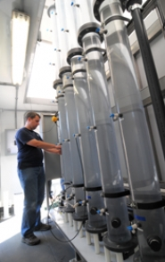 by:  VERN UYETAKE Tyler McCune uses the pilot ozone machine, which oxidizes contaminants by creating ozone in the water.  The new prototype mini plant, part of the Lake Oswego-Tigard Water Partnership, is located at the Lake Oswego water treatment plant in West Linn.