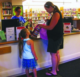 by: Tyler Graf CHECK OUT — St. Helens Public library assistant Nicole Woodruff helps a mother and daughter check out books Friday, Sept. 9.