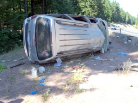 by: contributed image This 1997 Oldsmobile rests on its side along Highway 26 near Frog Lake east of Government Camp, following a crash Wednesday, Sept. 14, that injured a Gresham man and three others.