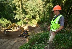 by: VERN UYETAKE David Kudna, a city engineering technician working as an inspector on the Lake Oswego Adult Community Center landslide repairs, stands about midway down a hillside where several tens of thousands of cubic yards of dirt and debris fell away last winter. Crews are working to stabilize the slope before heavy rains begin.