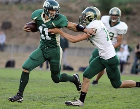 by: Chase Allgood Gaston quarterback David Carr (11) eludes the grasp of Regis defender Eric Olheiser during last Friday's non-league football game. Carr helped lead the Greyhounds to a 28-14 upset victory over the eighth-ranked Rams.