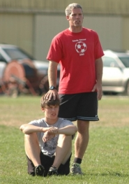 by: Kris Anderson Sandy boys soccer coach Garet Luebbert, above, directs an early-season practice, while Brody White, below, clears a ball out.