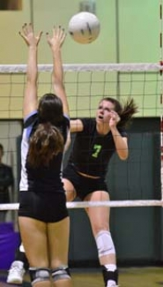 by: VERN UYETAKE Caitlin O'Neil spikes a ball past a Lakeridge blocker in Tuesday's home match.