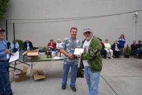 by: SUBMITTED PHOTO Tom Shields of Happy Valley, right, receives the Most Viewed Award from John Wilson of the Oregon City News after the Sept. 17 car show in downtown Oregon City. Shields showed his 1965 VW 21-window Samba Bus.