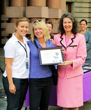 "by: David F. Ashton ONI Crime Prevention Coordinator Jenni Bernheisel presents the ""Neighborhood Watch Award"" to Woodstock Boulevard resident Terah Beth Varga, assisted by Portland City Commissioner Amanda Fritz."